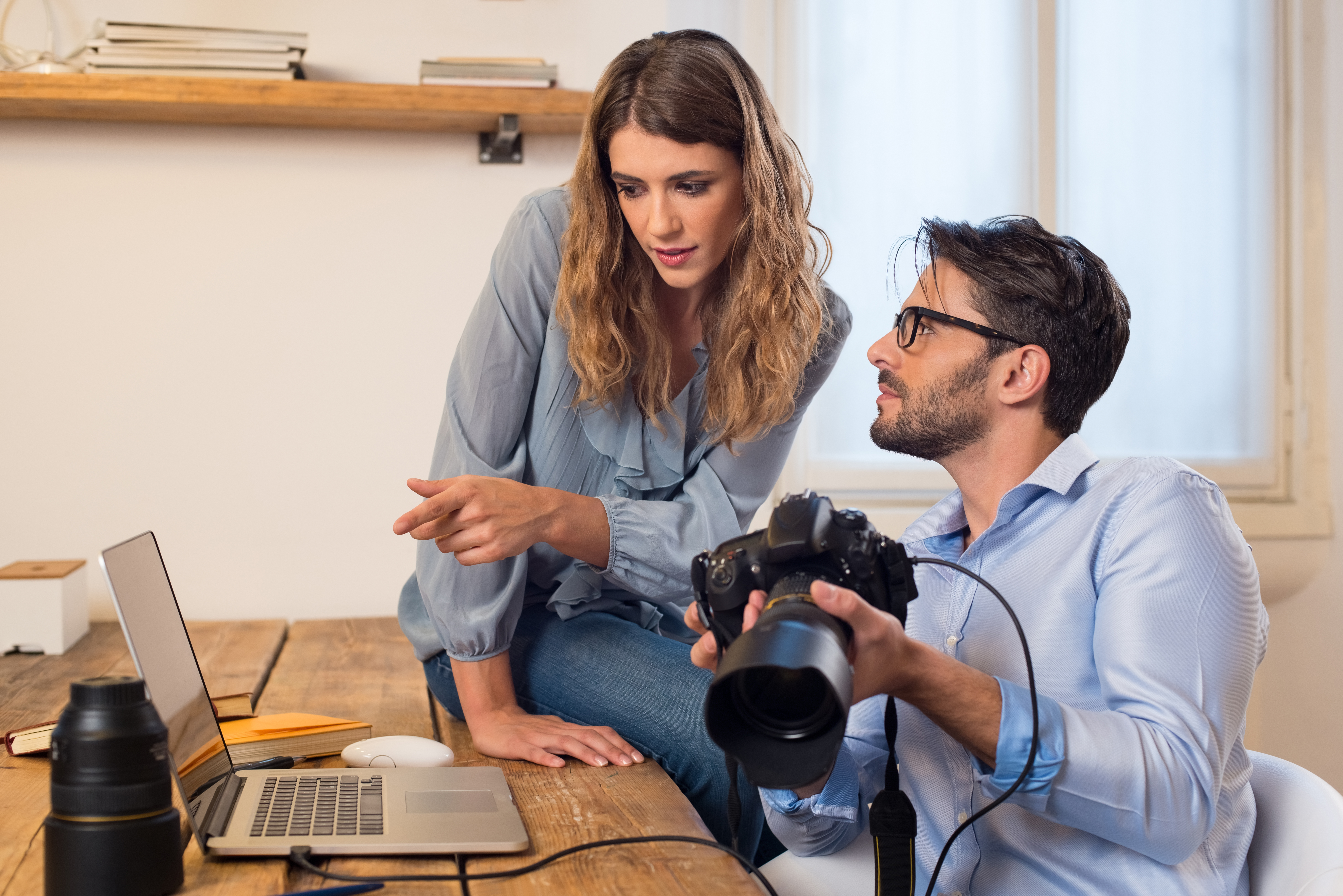 Photographer with model looking at photos